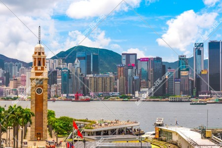 尖沙咀の時計台(尖沙咀鐘樓)と香港島の高層マンション・ビルの風景 その①