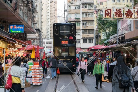 春秧街の露天街を走る香港トラムと買い物客
