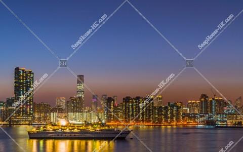 九龍半島の高層ビルの夕方の風景と観光クルーズ船